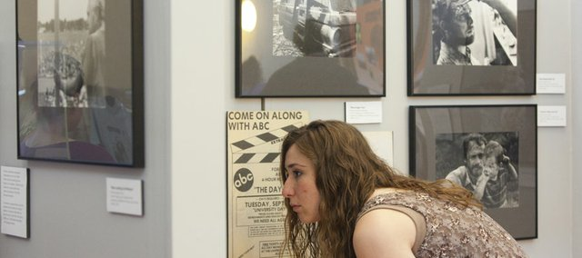 "Jami Roskamp, a Kansas University master's student from Sutter, Ill., gets close to look at some of the imagery from the filming of the ""The Day After"" that's on display Thursday in the Watkins Community Museum of History. As part of a class project, five students from a museum studies course at KU created the exhibit that shows the 1983 nuclear holocaust film's far-reaching effect toward raising fears about the threat of nuclear war during the Cold War."