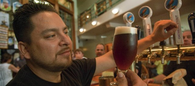 Ian Sotomayor, a bartender at Free State Brewery, looks over a 10 oz. glass of Full Kimono, an imperial red beer that was created by Free State, 23rd Street Brewery and Topeka's Blind Tiger Brewery for American Craft Beer Week.