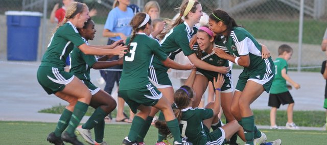 Free State senior Kylee Loneker is mobbed by teammates after scoring the winning goal with 2:59 left in the second overtime period, giving the Firebirds a 3-2 victory and a spot in the state playoffs on Thursday, May 17, 2012 in Topeka.