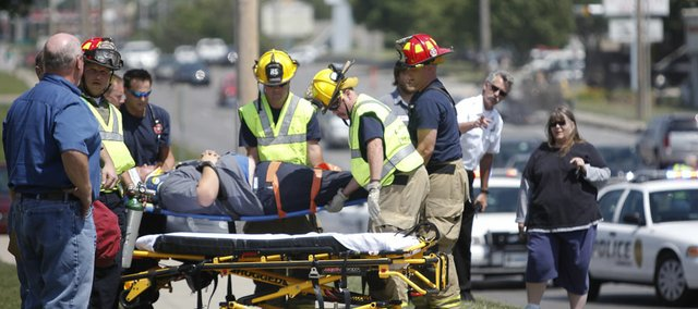 Emergency response personnel help load a man onto a stretcher after a five-car accident near the intersection of Sixth Street and Kasold Drive in the afternoon on Wednesday, May 23, 2012. Another person was transported to Lawrence Memorial Hospital with what were reported as life-threatening injuries.