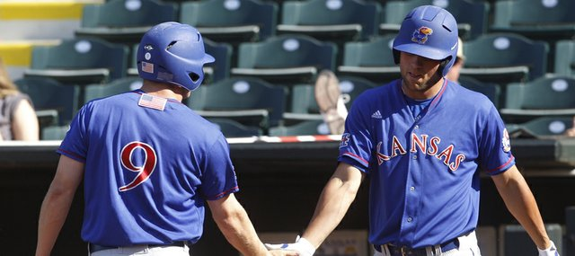 Kansas' Tucker Tharp (6) is congratulated by teammate Zac Elgie, right, after scoring against Texas A&M in the sixth inning of a Big 12 conference tournament college baseball game in Oklahoma City, Wednesday, May 23, 2012. Texas A&M won 10-4, but will face the Jayhawks in a rematch today after KU defeated the Texas Longhorns, 4-2.