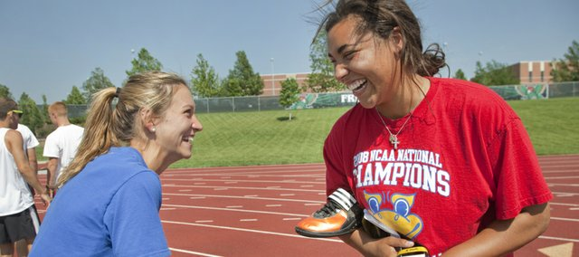Free State thrower Brie Mingus, right, who will be competing in the shot put and discus at this weekend's Class 6A state track meet, visits with teammate Courtney Huffman, who will be running the 4x400, before practice Wednesday, May 23, 2012, at FSHS.