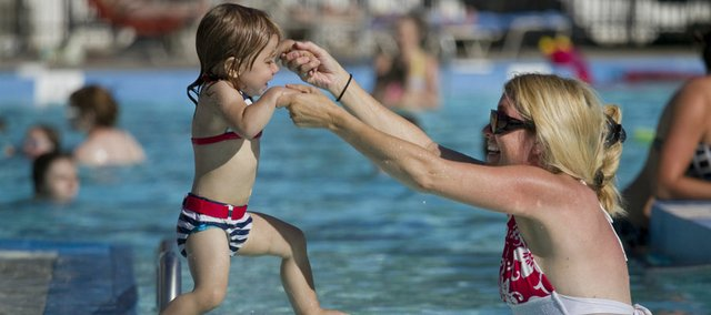 Jacey Yanek helps her 21-month-old daughter, Reagan, jump into the water Wednesday at the Lawrence Outdoor Aquatic Center, 727 Ky., in this June 2011 file photo.