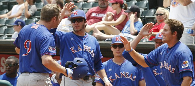 Kansas' Tucker Tharp (9) is greeted by teammates outside the dugout after hitting a home run against Missouri in the third inning. It was one of KU's few highlights in a 12-2 loss to the Tigers on Saturday in the Big 12 tournament in Oklahoma City.