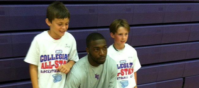 Kansas University's Elijah Johnson, center, poses with a pair of young participants in the KC Gym Rats Collegiate All-Star Camp on Monday, May 28, 2012, in Overland Park.