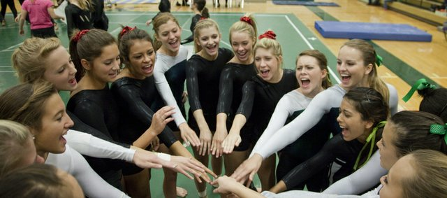 Free State and Lawrence High girls gymnastics team members gather for a cheer before competition in the Free State Invitational gymnastics meet Saturday, Sept. 24, 2011, at FSHS.