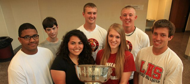 Lawrence High athletes, front row from left, Isaiah Ross (football, bowling), Darinka Delatorre (bowling, track), Kailey Wingert (volleyball), Troy Willoughby (baseball, basketball), and back row from left, Riley Gentry (bowling), Cameron Solko (football, baseball), and Garrett Cleavinger (football, baseball) pose with the World Company Cup, the tangible reward for edging Free State, 14.5 points to 13.5, during the 2011-2012 school year. It's the first time LHS has won the trophy.