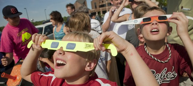 Using filtered glasses, Drew Bradford, 9, left, and Michael Uhler, 9, both of Lawrence, gaze at the sun and a view of the Venus transit, where Venus, appearing as a small black dot, crosses between the sun and Earth. People viewed the rare event Tuesday near the Lied Center. The last transit took place in 2004, and we won't see another until 2117.