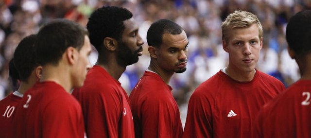 Kansas newcomer Perry Ellis, center, listens while in a team huddle between Justin Wesley, left, and fellow freshman Zach Peters as they prepare for a workout at Bill Self's basketball camp on Monday, June 11, 2012 at the Horejsi Center.