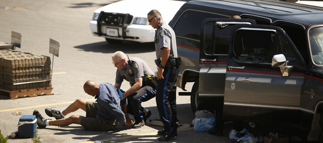 Police handcuff a man in the parking lot of Wal-Mart, Sixth and Congressional, on Wednesday, June 13, 2012.