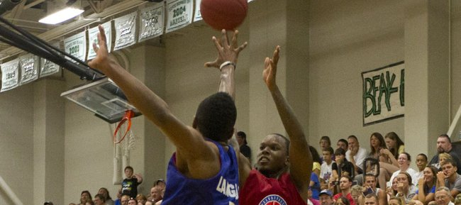 Russell Robinson fires a three over the outstretched arm of Keith Langford during the Rock Chalk Roundball Classic held Thursday, June 14, 2012, at Free State High.