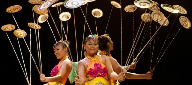 Lin Xiaoyu, left, and Yang Lei, members of the Fabulous Chinese Acrobats, balance spinning discs on poles during a performance at Liberty Hall Monday, June 18, 2012. Proceeds from the show went to the Lawrence Community Shelter.