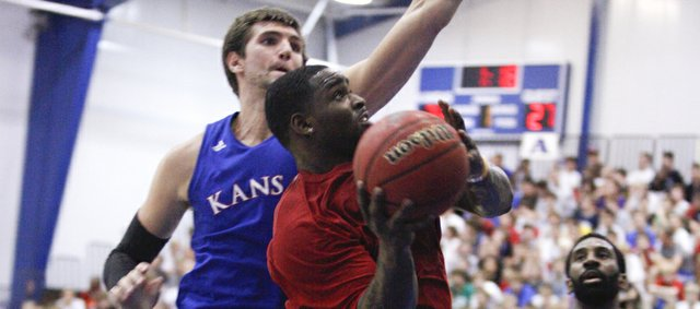 Former Kansas guard Sherron Collins heads to the bucket under center Jeff Withey during a scrimmage on Wednesday, June 20, 2012 at the Horejsi Center. Nick Krug/Journal-World Photo