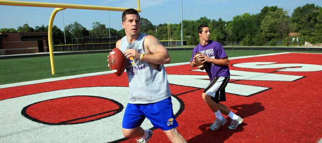 Lawrence High quarterback Brad Strauss, right, works out with former Kansas University quarterback Jordan Webb on Friday, June 29, 2012, at LHS. Strauss has tried to prepare for his senior season in the fall by spending much of the spring and summer training with Webb.