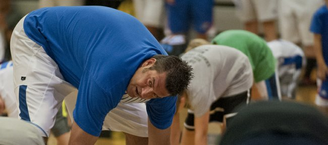 Former KU player Mark Randall, left, leads a warm-up exercise during the Cole Aldrich basketball camp Monday, July 9, 2012, at Olathe Northwest High School.