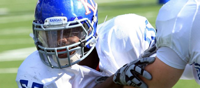 KU linebacker Michael Reynolds (55) works against a defensive lineman during practice on Tuesday, April 17, 2012, at the KU practice fields.