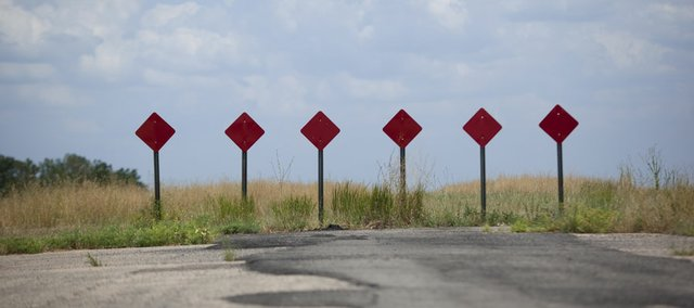 Six road blocks that mark the end of the roadway at the South Lawrence Trafficway stand on Tuesday, July 10, 2012. The Kansas Department of Transportation is planning to go ahead with a six-mile, four-lane extension to Kansas Highway 10 next year.