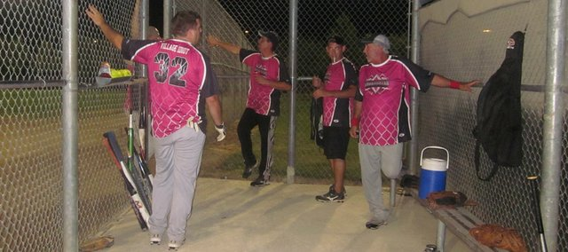 Members of the softball team Sons of Pitches stretch and talk before their first game of the Heatstrokers Marathon Friday at Clinton Sports Complex. The Heatstrokers Marathon was an overnight slow-pitch softball tournament to raise money for a Lawrence team to go to the world tournament in October in Orlando, Fla.
