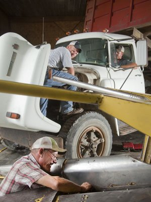 Kent Nunemaker, of Lawrence, foreground, co-owner of Nunemaker-Ross farms, installs new belts on a silage cutter Friday while Lyle Nunemaker, Lawrence, center, and C.J. Bunce, of Perry, repair brakes on a 1978 International truck. Friday's rain delayed a plan to cut corn for silage but provided an opportunity to do some farm equipment repairs.