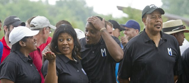 Former KU basketball player Mario Chalmers, now a member of the Miami Heat, second from right, and family members get wet during a rainfall before the start of the Mario Chalmers Foundation National Championship Classis golf tournament Friday, July 13, 2012, at Alvamar. Family members from left, all of Miami, are Almaire Chalmers, Mario's mother, his sister Roneka, Mario and his father Ronnie.