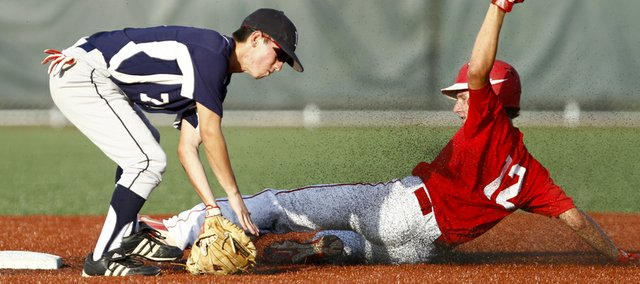 Lawrence Raiders second baseman Trevor Champagne catches the ball — and a spray of rubber turf — as Topeka Capitals runner Derrick Bohn slides safely into second during the fifth inning Tuesday, July 17, 2012, at Lawrence High.
