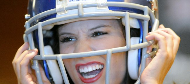 Kansas cheerleader Jordan Snyder jokes around with friends while wearing a football helmet at the Big 12 college football media days on Tuesday, July 24, 2012, in Dallas.