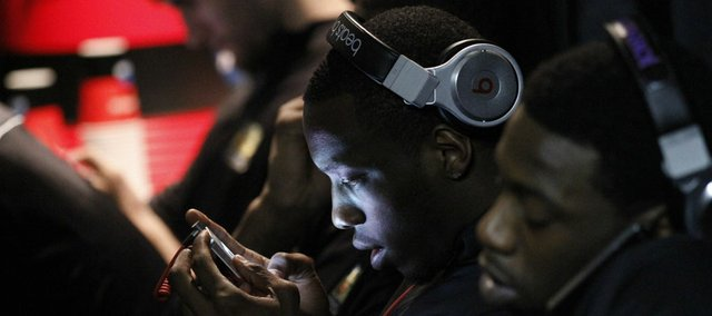 Kansas University basketball player Tyshawn Taylor, center, texts on his phone during NCAA Final Four events last spring. In this dimly lit image, I had reached my largest aperture of f2.8 and my hand-holdable limit of a 1/25th shutter speed. My only choice was to increase my ISO to 5000. I was willing to accept a decrease in image quality just to obtain the photograph. Being aware of what ISO you are using can keep you from experiencing unintended loss of quality in your photos.