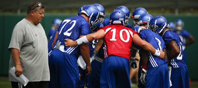 Head coach Charlie Weis walks past as quarterback Dayne Crist pulls the offense into the huddle during practice on Thursday, Aug. 2, 2012.