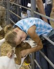 Holly Vesecky, 11, of Baldwin City, hugs her family's goat, PUPPYDOG FACE, before the start of the livestock auction Saturday at the Community Building at the Douglas County Fairgrounds. Holly had raised the goat since it was a baby, and was saying goodbye before it was auctioned off.