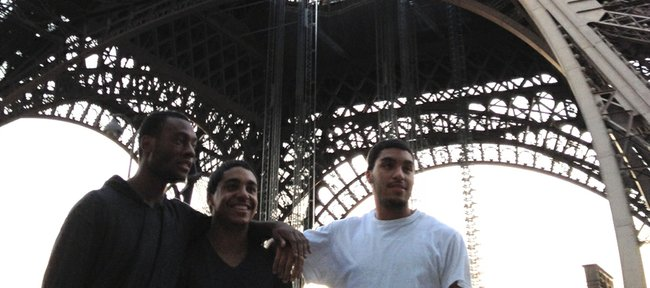Kansas guard Naadir Tharpe, left, and guard Niko Roberts, right, stop for a photo in front of the Eiffel Tower in Paris with Niko's younger brother Justin on Thursday, Aug. 9, 2012.