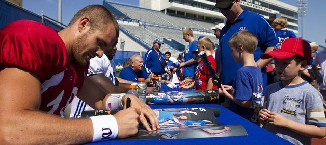 Greyson Heinan, 6, Lawrence, watches as Kansas quarterback Dayne Crist signs a poster during the autograph portion of Fan Appreciation Day on Saturday, Aug. 11, 2012, at Memorial Stadium.