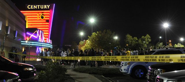 People gather outside the Century 16 movie theatre in Aurora, Colo., at the scene of a mass shooting early Friday morning, July 20, 2012. Police Chief Dan Oates says 14 people are dead following the shooting at the suburban Denver movie theater. He says 50 others were injured when gunfire erupted early Friday at the Aurora theater. Oates says a gunman appeared at the front of one of the Century 16 theaters.
