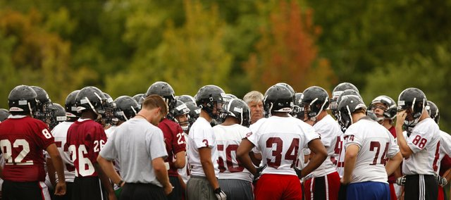 Lawrence High head coach Dirk Wedd talks with his team from the center of the huddle during the first day of practice on Monday, Aug. 13, 2012 at Lawrence High.
