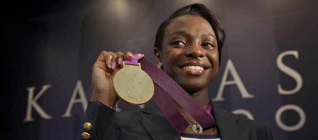 Kansas University runner and Olympic athletic Diamond Dixon shows off her gold medal during a press conference at KU's Anderson Family Football complex on Wednesday.