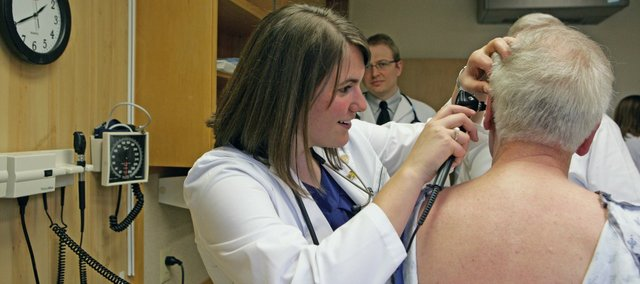 Jill Corpstein, a student at the Kansas University School of Medicine in Salina, examines a patient as part of her training. The school, which started one year ago, accepts eight students a year and its mission is to increase the number of physicians in rural areas.