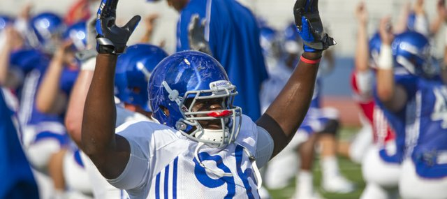 Kansas defensive lineman Keba Agostinho stretches during warm-up exercises at the Fan Appreciation Day open practice Saturday, Aug. 11, 2012, at Memorial Stadium.