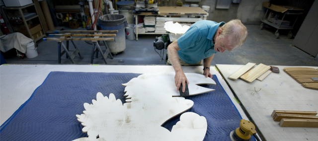 D.W. Acker, a graphic artist for Kansas Athletics works to sand the edges of a Jayhawk cut from wood on Thursday, June 28, 2012 in his shop located on the lower level of the parking facility next to Allen Fieldhouse. Most of those who tour the fieldhouse and its adjoining facilities aren't aware of how many of the decorative displays and tributes to sports legends are produced or even conceived. Acker's handiwork and creativity can be seen throughout in fixtures small and large.