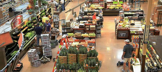 Workers put the finishing touches on grocery displays Friday at the new Dillons store at 1740 Mass. The store is set to open its doors to the public at 7 a.m. Sunday.