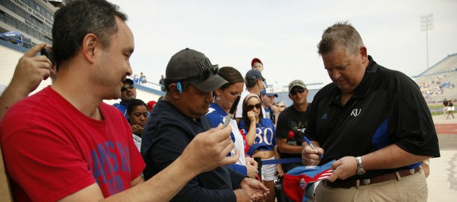 Kansas head coach Charlie Weis signs an autograph for Ivan Valdivia, Shawnee following the Spring Game on Saturday, April 28, 2012 at Kivisto Field. At left is Eric Smith, also of Shawnee.