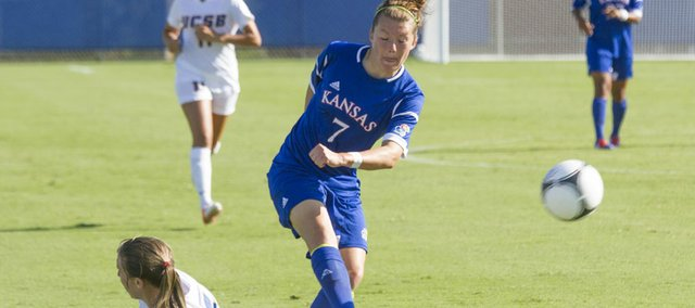 Kansas' Whitney Berry (7) kicks the ball past sliding UC Santa Barbara's Lindsay Gankema during their soccer match Friday, August 17, 2012 at KU.