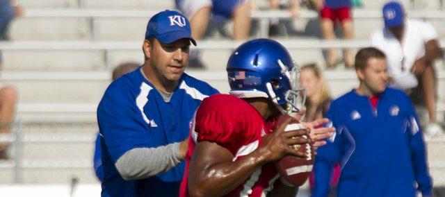 Kansas quarterbacks coach Ron Powlus harasses quarterback Michael Cummings during a passing drill at the Fan Appreciation Day open practice Saturday, Aug. 11, 2012, at Memorial Stadium.