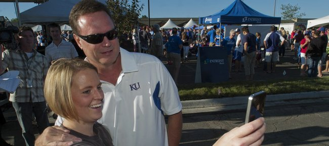 Kansas fan Jennifer Coughenour snaps a quick photo with KU men's basketball coach Bill Self on Friday before the KickOff at Coringth Square in Prairie Village for the KU football season.