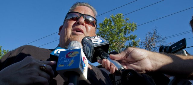 Kansas football coach Charlie Weis talks with the media before taking the stage Friday during the KickOff at Coringth Square in Prairie Village for the Kansas football season.