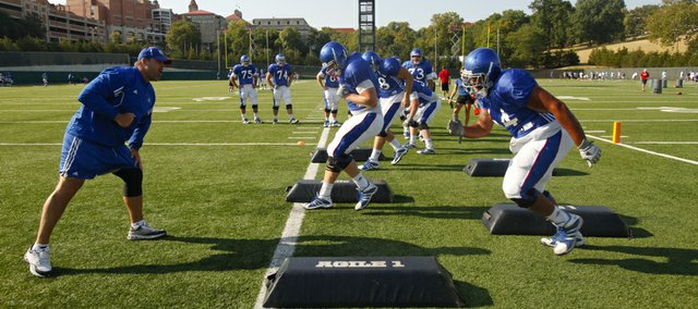 Offensive line coach Tim Grunhard works his players through drills during practice on Wednesday, Aug. 15, 2012.