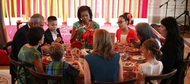 "First lady Michelle Obama sits with Michael Prados, left, from Louisiana, and Ilianna Gonzales-Evans, right, from Washington, and others, during the first Kids' ""State Dinner,""Monday, Aug. 20, 2012, in the East Room of the White House in Washington."