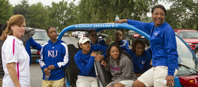 Kansas women's basketball coach Bonnie Henrickson, left, hangs out with members of her team around a Jayhawk-themed golf cart before the start of the eighth annual Bonnie Henrickson Golf Tournament on Saturday, August 25, 2012, at Alavamar.