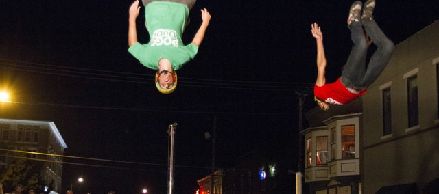 Mike Mena, left, and Mike Hughes of the Pogo Dudes perform back flips off of pogo sticks as a large crowd watches during the annual Buskerfest held in downtown Lawrence, Friday, August 24, 2012. The performances continue tomorrow.