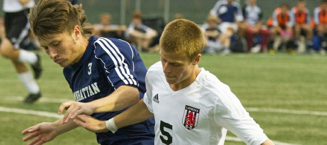 Lawrence High's Gavin Fischer (5) uses his body to shield the ball away from Manhattan's Jacob Stutheit (3) during their soccer match Friday, August 24, 2012, at LHS.
