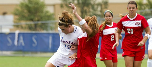 Kansas' Caroline Kastor, left, and UNLV's Justine Sauder each get a foot on the ball as they stretch to try to gain possession during their soccer match Sunday, August 26, 2012, at the Jayhawk Soccer Complex.