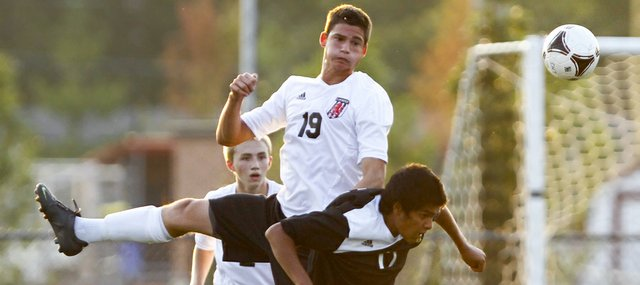 Lawrence High defender Dalen Reed battles for the ball with Topeka High forward Garet Campion during the first half on Tuesday, Aug. 28, 2012, at LHS.